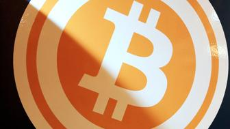 A bitcoin logo is displayed on the BMEX bitcoin exchange's Robocoin-branded automated teller machine (ATM) at The Pink Cow restaurant and bar in Tokyo, Japan, on Wednesday, June 18, 2014. Bitcoin, proposed by an anonymous programmer or programmers in 2008, has drawn entrepreneurs and retailers looking to popularize it as a low-cost alternative to established payment systems, supplanting credit cards to international wire transfers. Photographer: Yuriko Nakao/Bloomberg via Getty Images