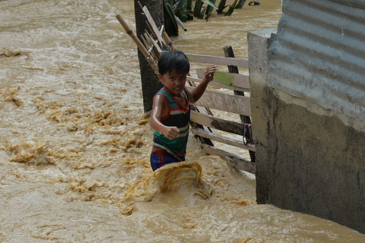 A child wades through floodwaters near his residence at a village in Santa Rosa town, Nueva Ecija province, north of Manila o