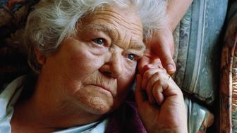 Elderly woman looking pensive, holding young woman's hand,close-up
