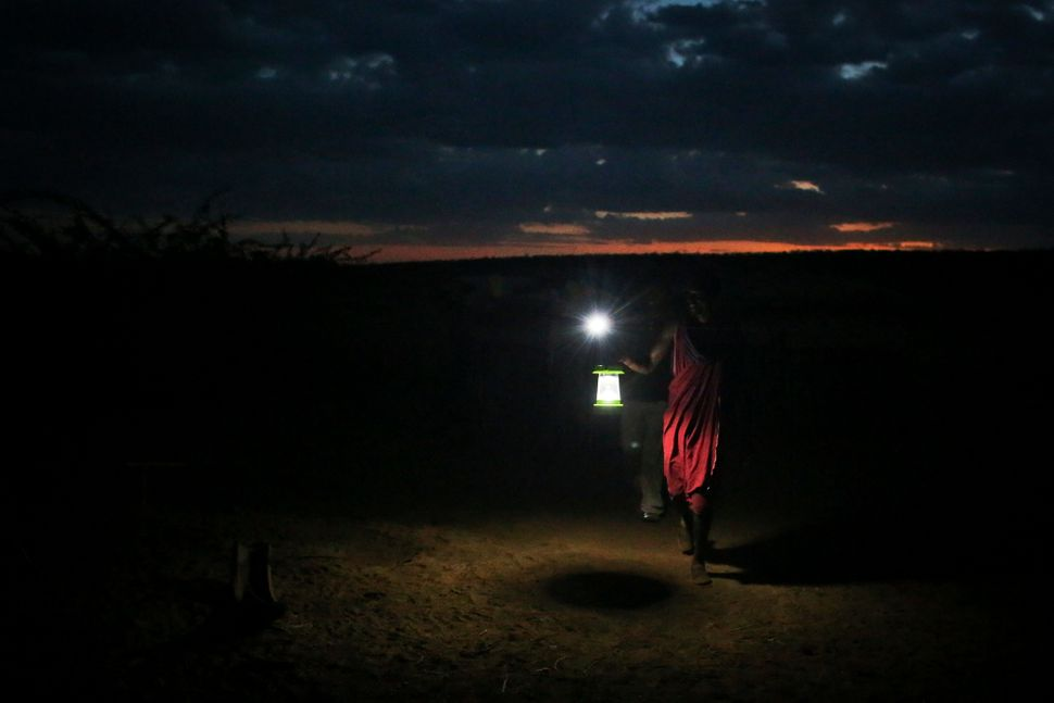 A Masaai man holds up a newly obtained solar lamp to keep predators away from the herds. The Masaai are at the center of inno