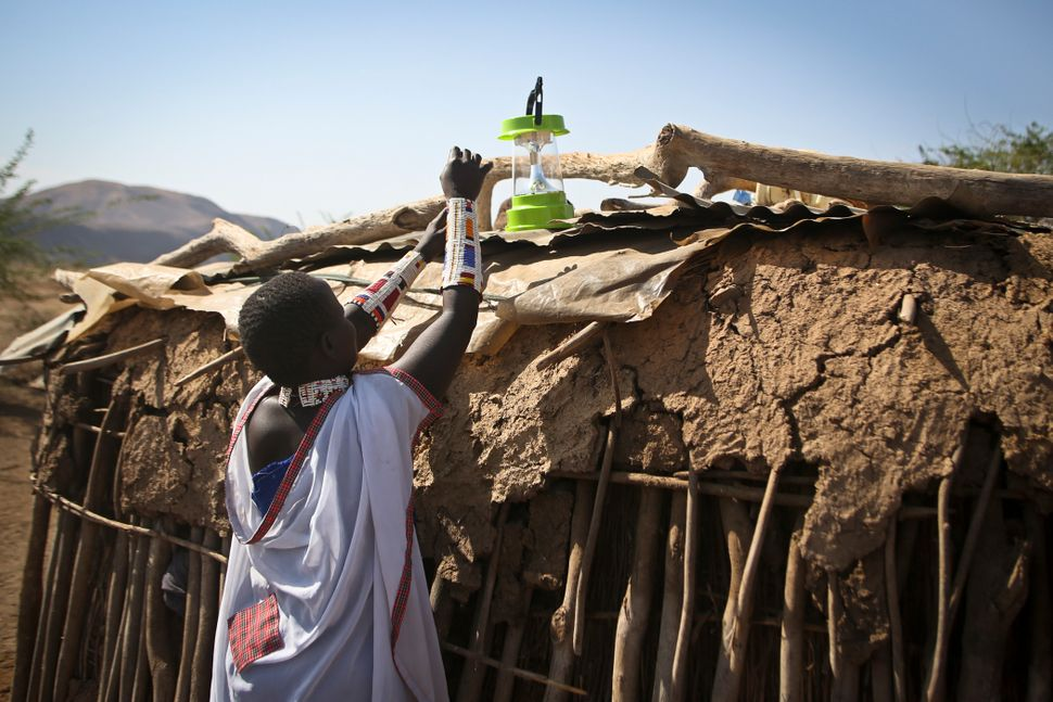 A Maasai woman sets up a solar light to recharge in the village of Koora, Kenya.
