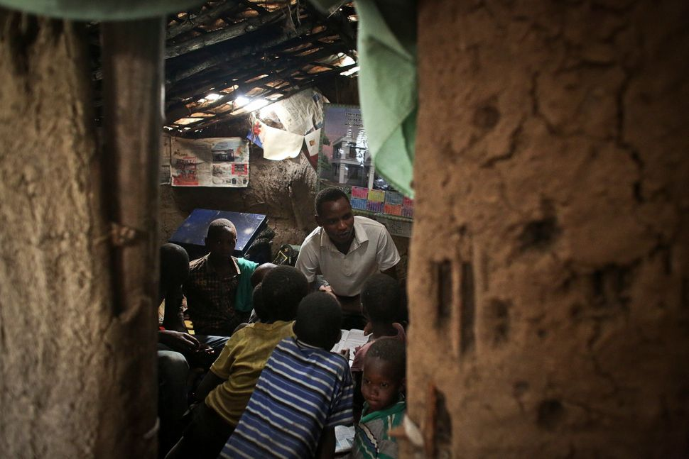 John Keko Mututua, 16, studies with children from the village in his small hut in the town of Suswa, Kenya. Power provid