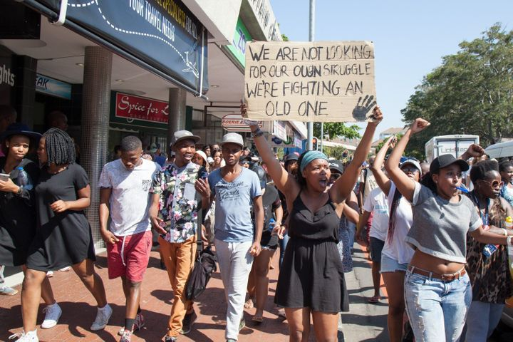 """""""We are not looking for our own struggle. We're fighting an old one,"""" a student's placard reads."""