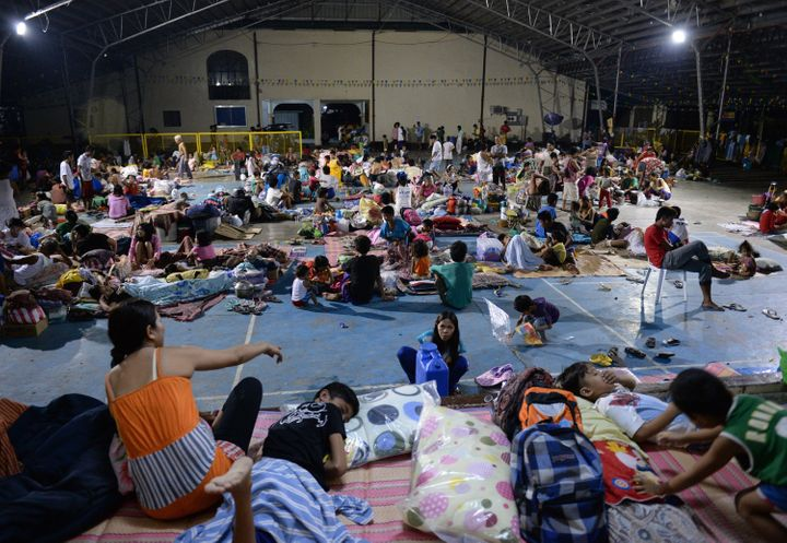 People evacuated from their homes rest inside a makeshift shelter in a school in Cabanatuan City, Philippines, on Oct. 19, 20