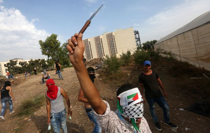 A young Palestinian raises a knife during clashes with Israeli security forces (not pictured) in the West Bank city of Tulkar