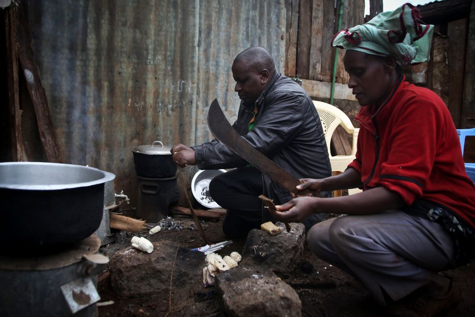Keneth Ndua and his sister Jane Muthoni use a cookstove in Ngawa, Kenya, Saturday, Aug. 8, 2015.