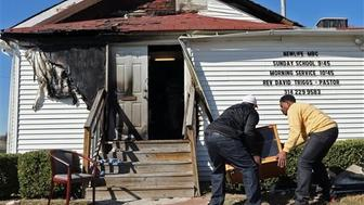 In this Sunday, Oct. 18, 2015 photo, Deacon Clinton McMiller, left, and Pastor David Triggs carry a cabinet back into the church after an outdoor service due to a fire at the New Life Missionary Baptist Church in St. Louis. Someone has been setting fire to predominantly black churches in the St. Louis area, and investigators are trying to determine if the arsonist is targeting either religion or race.