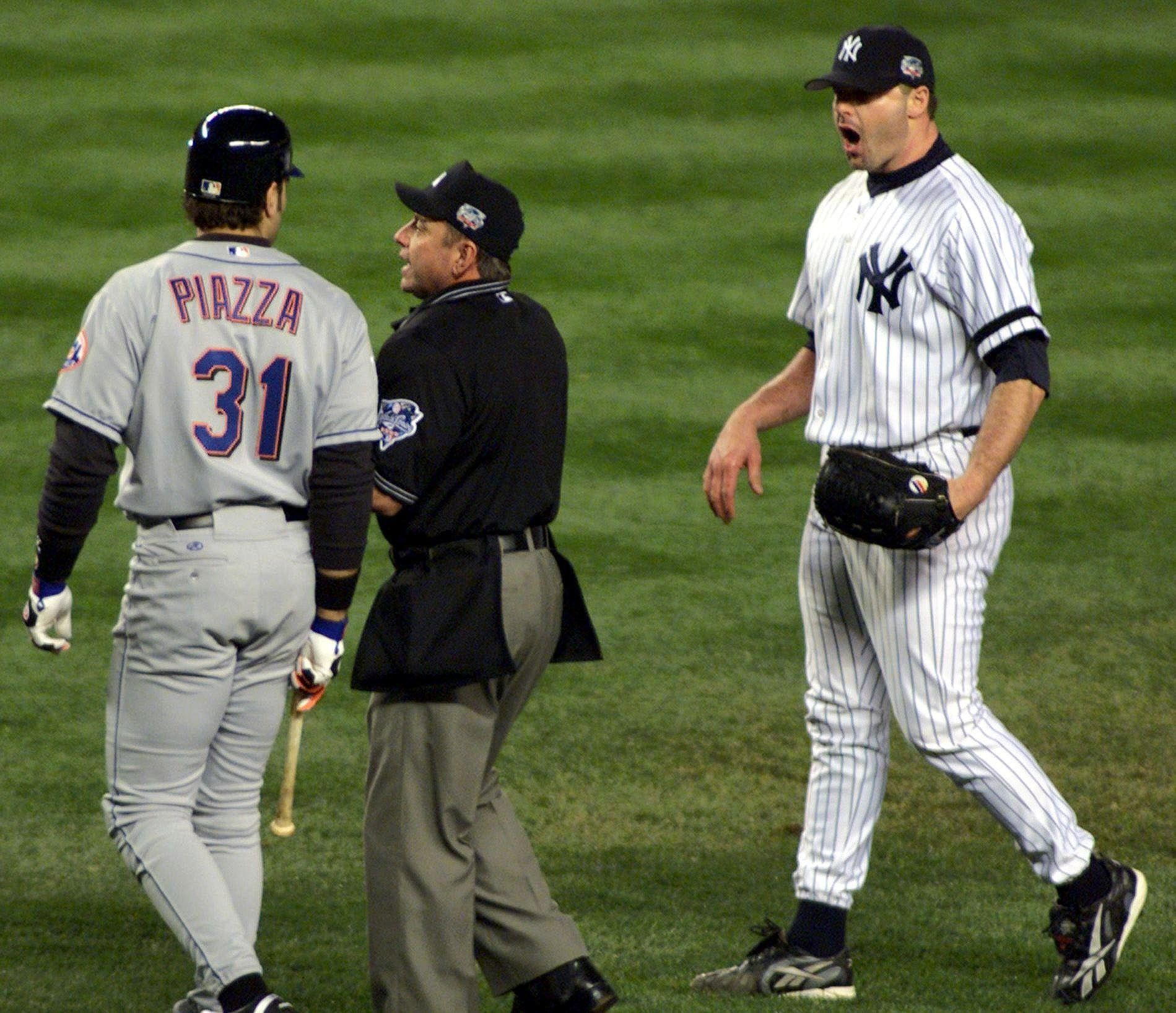 NEW YORK, UNITED STATES:  Home plate umpire Charlie Reliford (C) comes between New York Mets' catcher Mike Piazza (L) and New York Yankees' pitcher Roger Clemens during the first inning of the Second Game of the World Series in New York City 22 October, 2000. Clemens threw a piece of Piazza's broken bat at Piazza as he ran to first base causing a dugout clearing altercation between the two teams.  AFP PHOTO/Don EMMERT (Photo credit should read DON EMMERT/AFP/Getty Images)