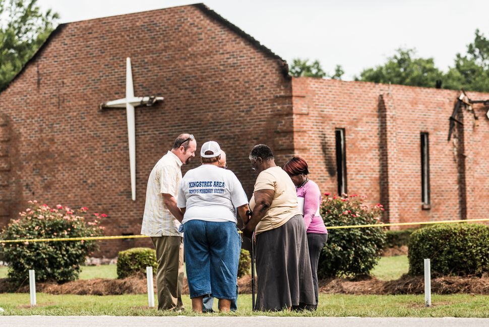 People pray near the burned ruins of the Mt. Zion AME Church July 1, 2015, in Greeleyville, South Carolina.