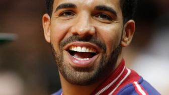 Recording artist Drake smiles as he sits courtside at the Staples Center during an NBA basketball game between the Los Angeles Clippers and Golden State Warriors, Tuesday, March 31, 2015, in Los Angeles. The Warriors won 110-106. (AP Photo/Danny Moloshok)