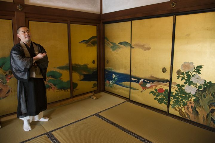 A monk at Shunkoin stands in front of the temple's sliding door panels, which were painted by artist Eigaku Kano.