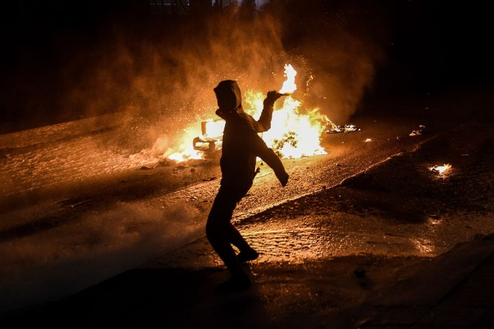 A fire burns in the background as a left-wing militant throws a molotov cocktail toward a water cannon during a demonstration