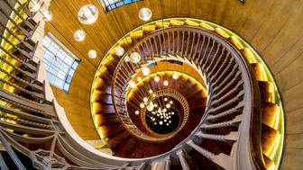 UNVERFIED Looking down into the newly refurnished Heals department store staircase on Tottenham Court Road in London; this wonderful staircase now boasts a 64 arm Bocci Chandelier. Heal's is a British furniture and furnishing store chain comprising six stores, selling a range of furniture, lighting, accessories, home and garden wares. For over a century it has been known for promoting modern design and employing talented young designers.