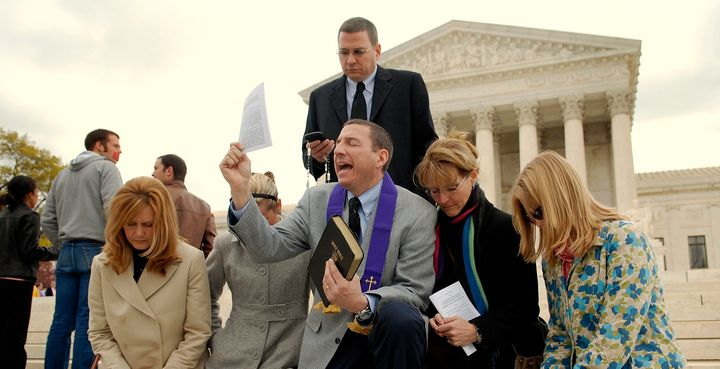 The Rev. Robert Schenck leads anti-abortion advocates in prayer on the steps of the Supreme Court on April 18, 2007.
