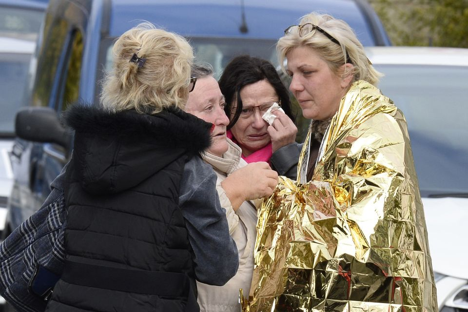 People comfort a survivor after a bus transporting retirees on a day trip collided with a truck and caught fire in Puiss