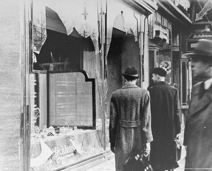 Germans pass by the smashed windows of a Jewish-owned shop. The aftermath of Kristallnacht (Night of Broken Glass) 9-10 Novem