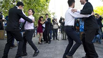 Gay rights activists dance outside the Registry Office, after the civil marriage ceremony of Roxana Ortiz and Virginia Gomez in Santiago on Octubre 22, 2015. The Chilean government launched a campaign Tuesday to promote a new civil union law that will go into effect Thursday and apply to both heterosexual and homosexual couples. The law, long-sought by advocacy groups, is seen as a first step towards allowing gay marriage in the heavily Catholic country.    AFP PHOTO / MARTIN BERNETTI        (Photo credit should read MARTIN BERNETTI/AFP/Getty Images)