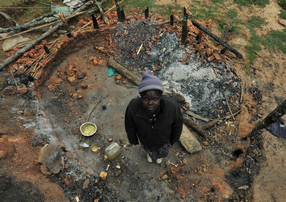 Selly Rotich stands in what used to be her kitchen. She says it was destroyed hours earlier by KFS officers.