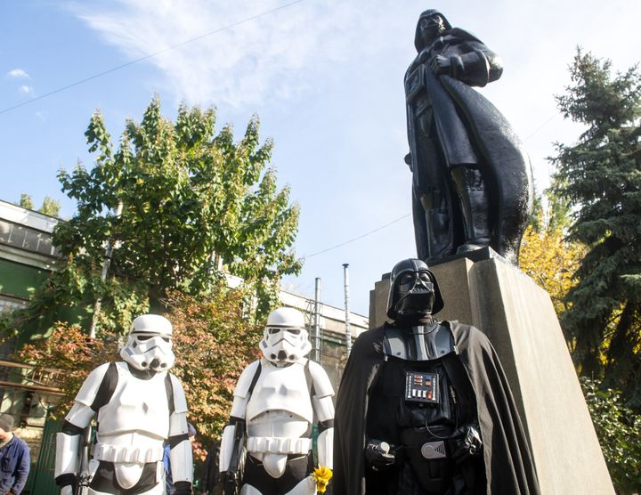 Costumed Storm Troopers and Darth Vader take in the unveiling of the converted statue.