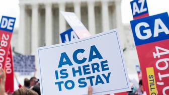UNITED STATES - JUNE 25: Affordable Care Act supporters wave signs outside the Supreme Court after the court upheld court's Obamacare on Thursday, June 25, 2015. (Photo By Bill Clark/CQ Roll Call)