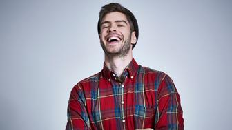 Portrait of young bearded man with tattooed arms in red and blue check shirt and beanie, laughing with head back and eyes shut