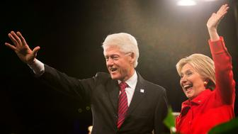Hillary Clinton, former U.S. secretary of state and 2016 Democratic presidential candidate, right, waves to supporters with husband Bill Clinton, former U.S. president, at the conclusion of the Jefferson-Jackson Dinner in Des Moines, Iowa, U.S., on Saturday, Oct. 24, 2015. With Vice President Joe Biden officially out of the presidential race, the nation's first nominating contest between front-runner Clinton and Senator Bernie Sanders is gaining steam, according to a new Bloomberg Politics/Des Moines Register Iowa Poll. Photographer: Daniel Acker/Bloomberg via Getty Images