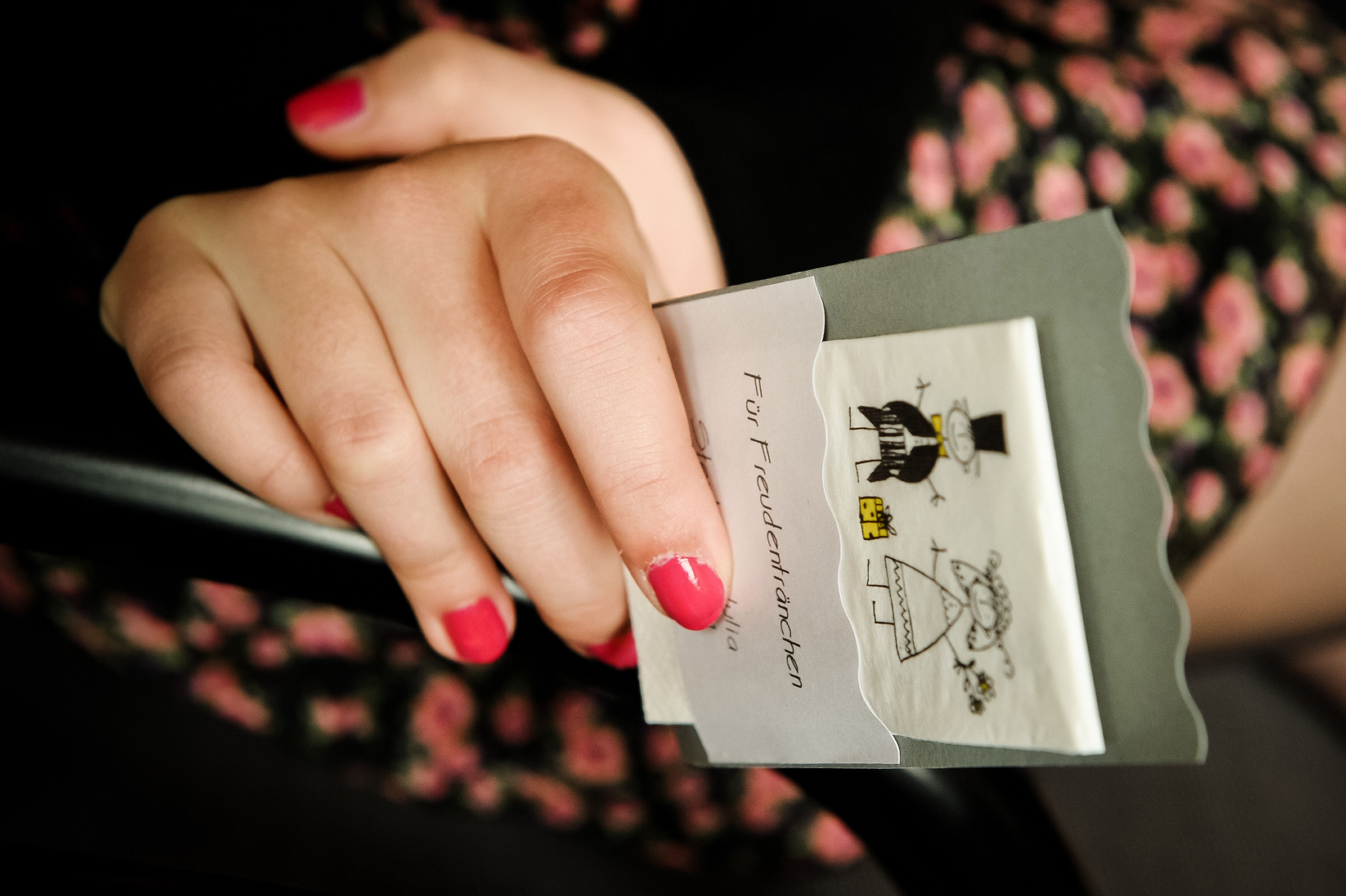Woman with nail polish holding wedding card