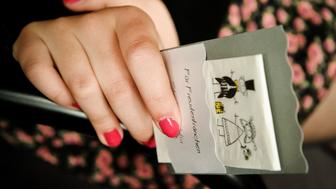 Woman with nail polish holding wedding card