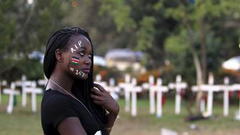 "A student wearing facepaint walks past wooden crosses in memory of the Garissa university students who were killed by gunmen, at a memorial concert at the ""Freedom Corner"" in Kenya's capital Nairobi on April 14, 2015. Photo courtesy of REUTERS/Noor Khamis