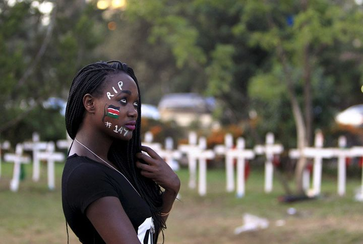 A student wearing face paint walks past wooden crosses in memory of the Garissa university students who were killed by gunmen