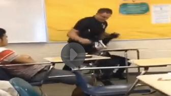 An officer pulls a student from her desk at Spring Valley High School in South Carolina