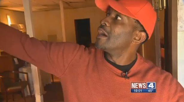 Pastor Triggs points out the damage inside his church, which he says will cost more than $20,000 to fix.