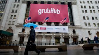Pedestrians walk past a GrubHub Inc. banner on the exterior of the New York Stock Exchange in New York, U.S., on Friday, April 4, 2014. GrubHub Inc., which lets hungry city dwellers order food online, raised a higher-than-expected $192 million in an initial public offering, after pricing the shares above a marketed range. Photographer: Jin Lee/Bloomberg via Getty Images