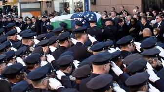 NEW YORK, NY - DECEMBER 27:  Pallbearers carry the casket to a hearse during the funeral of slain New York City Police Officer Rafael Ramos, one of two officers murdered while sitting in their patrol car in an ambush in Brooklyn last Saturday afternoon on December 27, 2014 in New York City. Thousands of fellow officers, family, friends and Vice President Joseph Biden are expected at the church in the Glendale neighborhood of Queens for the funeral.  (Photo by Kevin Mazur/Getty Images)