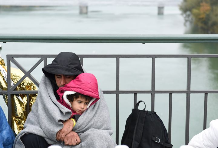 A man and child take shelter from the cold as they wait to cross the Austrian-German border.