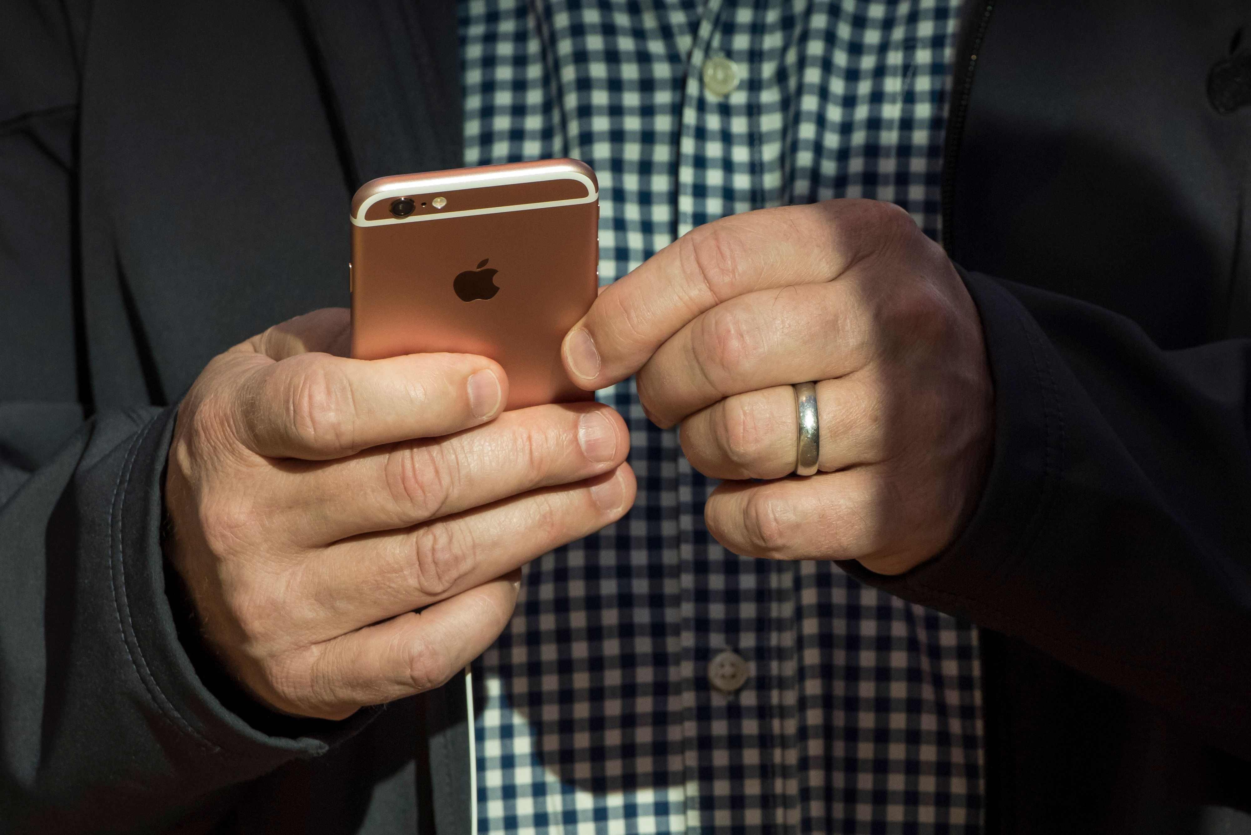 A customer looks at a Apple Inc. iPhone 6s at an Apple store in Palo Alto, California, U.S., on Friday, Sept. 25, 2015. From Sydney to New York, some of the Apple faithful waited in lines for more than two weeks to be among the first to receive the new iPhone 6s and 6s Plus. Photographer: David Paul Morris/Bloomberg via Getty Images