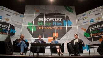 Michael Dell, chairman and chief executive officer of Dell Inc., right, speaks as Steve Kaufer, chief executive officer of TripAdvisor, from left, Jeffrey 'Jeff' Housenbold, chief executive officer of Shutterfly and Carley Roney, co-founder of Knot Inc., listen during a panel discussion at the South By Southwest (SXSW) Interactive Festival in Austin, Texas, U.S., on Friday, March 7, 2014. The SXSW conferences and festivals converge original music, independent films, and emerging technologies while fostering creative and professional growth. Photographer: David Paul Morris/Bloomberg via Getty Images