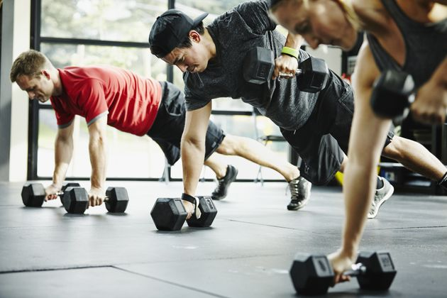 Group of friends doing pushups with dumbbells in crossfit