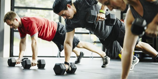 Group of friends doing pushups with dumbbells in crossfit gym