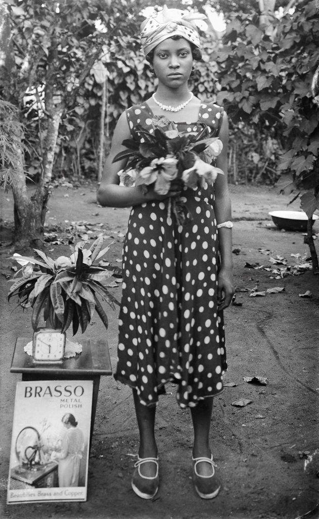 "Woman standing with flowers; clock on table;""Brasso metal polish"" [Dame Merry Oritsetimeyin Ehanire nee Cardigan (Osagie Ehan"