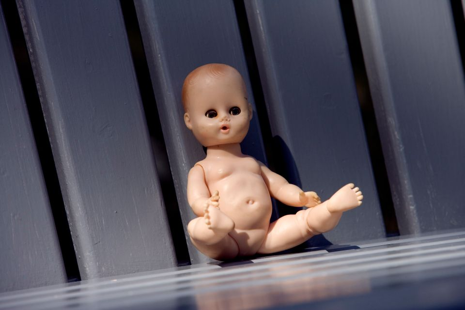 Child's doll on slatted bench