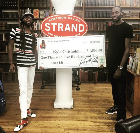 Israel presenting the winner of the 2015 #LiterarySwag contest, Kyle Chisholm, with a $1,500 check.