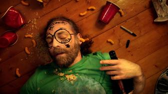 Man passed out at party laying on floor clutching bottle with stuff drawn on his face.