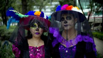 Women dressed as 'Catrina' pose for pictures at the Angel of Independence square before taking part in the Procession of the Catrinas along Reforma Avenue in Mexico City on October 25, 2015. Catrina is a cartoon character created by cartoonist Jose Guadalupe Posada and baptized by artist Diego Rivera, who popularized it and whose character is now part of Mexican culture during the celebrations of the Day of the Dead.   AFP PHOTO / Yuri CORTEZ        (Photo credit should read YURI CORTEZ/AFP/Getty Images)