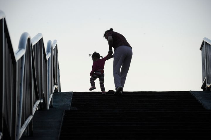A family makes their way along the steps of a footbridge in Beijing. China will officially end its longstanding one-chil