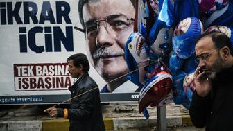 A balloon vendor walks past an election billboard of Turkish Prime Minister Ahmet Davutoglu during a Republic Day ceremony in Istanbul on October 29, 2015, ahead of November 1 general elections. Turkey is holding its second election in five months after the AKP, which has dominated the political scene for 13 years, lost its majority in a stunning election setback in June.  AFP PHOTO / DIMITAR DILKOFF         (Photo credit should read DIMITAR DILKOFF/AFP/Getty Images)