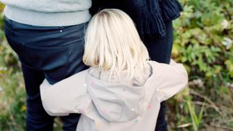 Rear view of little girl hugging parents legs