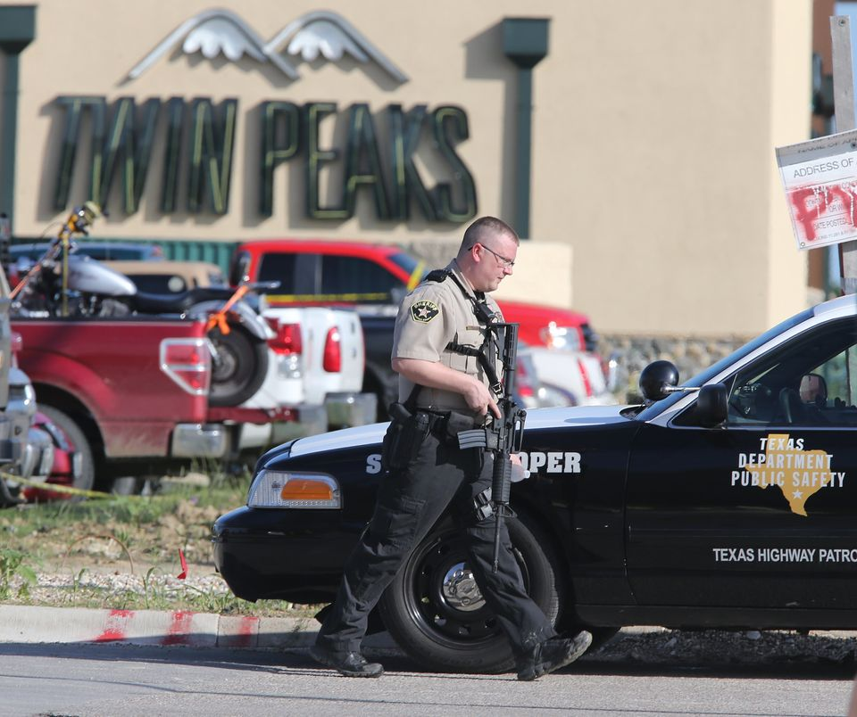 Authorities investigate a shooting in the parking lot of the Twin Peaks restaurant Sunday, May 17, 2015, in Waco, Texas. Auth