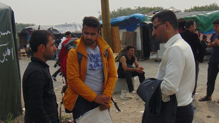 "Passarlay and a member of the Afghan Youth Movement UK talk to an Afghan refugee in the ""Jungle,"" a makeshift refugee camp in"