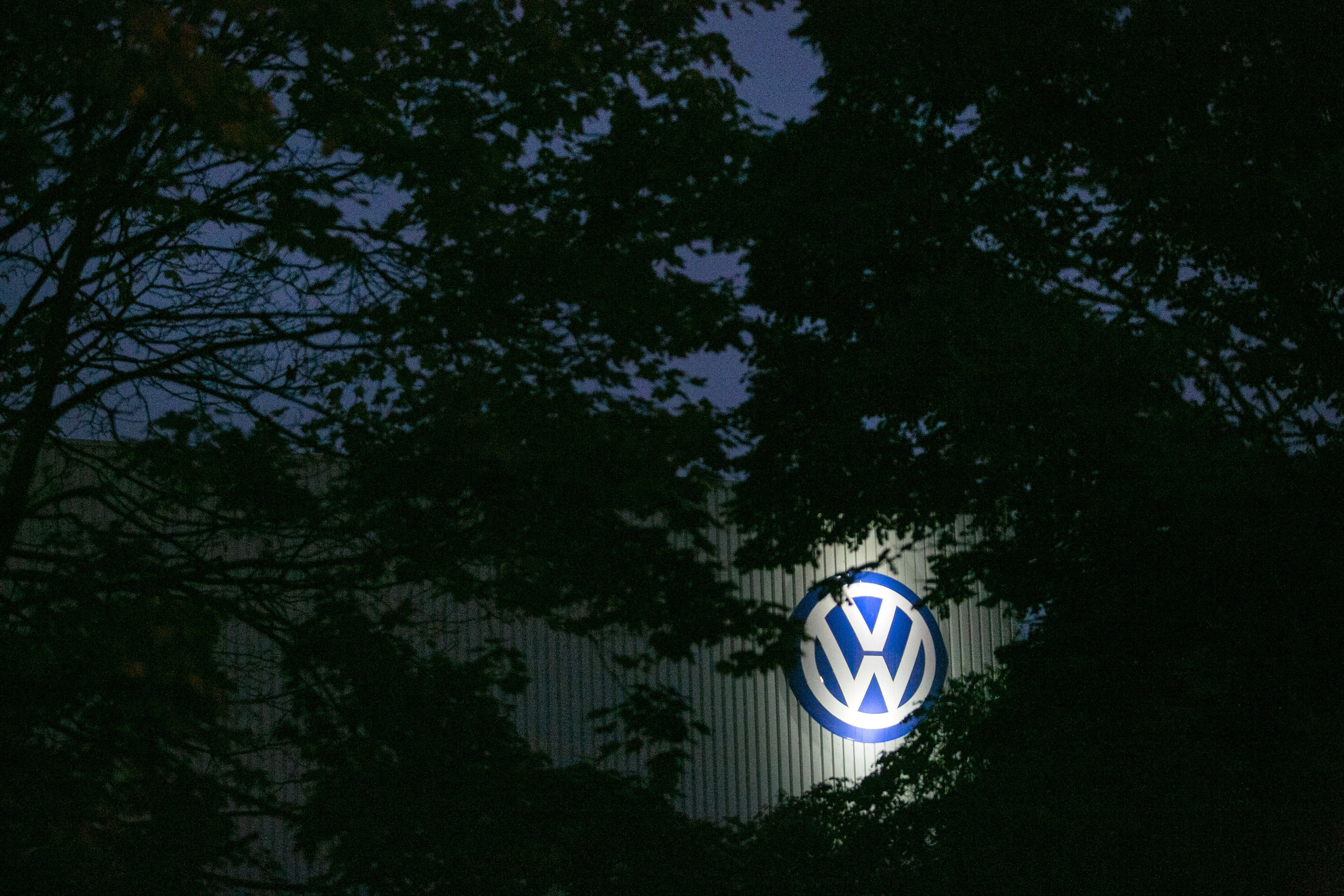 The Volkswagen (VW) logo sits illuminated on the exterior of the Volkswagen AG factory at night in Braunschweig, Germany, on Thursday, Oct. 22, 2015. The towns that became synonymous with Volkswagen AG's rise to the pinnacle of the auto industry are feeling the pinch of the diesel-emissions scandal, freezing spending on projects such as playgrounds amid the carmaker's abrupt fall from grace. Photographer: Krisztian Bocsi/Bloomberg via Getty Images